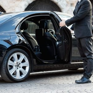 Corporate airport transfers driver opens car door